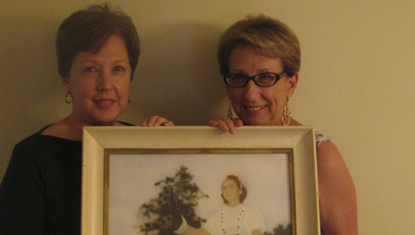 """Sisters Toni McMurphy, left, and Susan Moorehead hold a framed photo of their mother, former Blue Devils kicker Luverne """"Toad"""" Wise Albert."""
