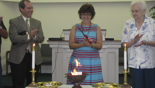 Dr. Cory Smith, left, the Rev. Diane Everette, center, and Marie Owens take part in a note burning service Sunday at Bethel United Methodist Church.