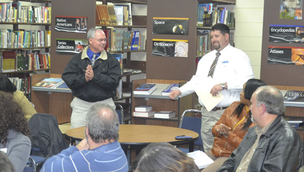 Escambia County High School principal Dennis Fuqua, right, introduces new ECHS football coach Royce Young, left, during Thursday's Escambia County Board of Education meeting at the ECHS library.|Photo by Justin Schuver