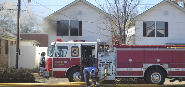 Smoke billows out a window as firefighters battle a fire at a Trammell Street apartment Wednesday afternoon.
