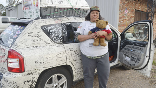 "Lisa Groves stands in front of her vehicle and shows off ""Hero Bear,"" a teddy bear that she allows veterans to hug for comfort. Groves said Hero Bear has several stains from veterans' tears. Her vehicle is covered in the signatures of veterans and other citizens who support her mission."