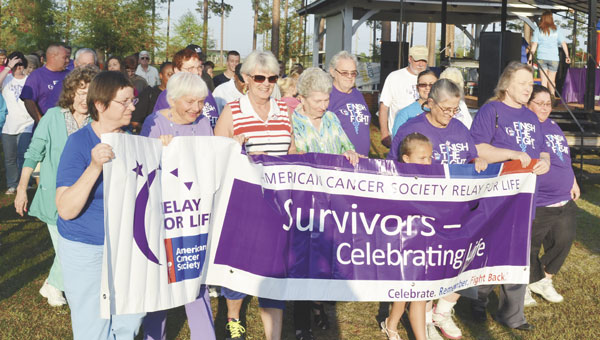 """Survivors, their caregivers and family members join in the """"Survivor Lap"""" to kick off Friday's Relay For Life at Tom Byrne Park."""