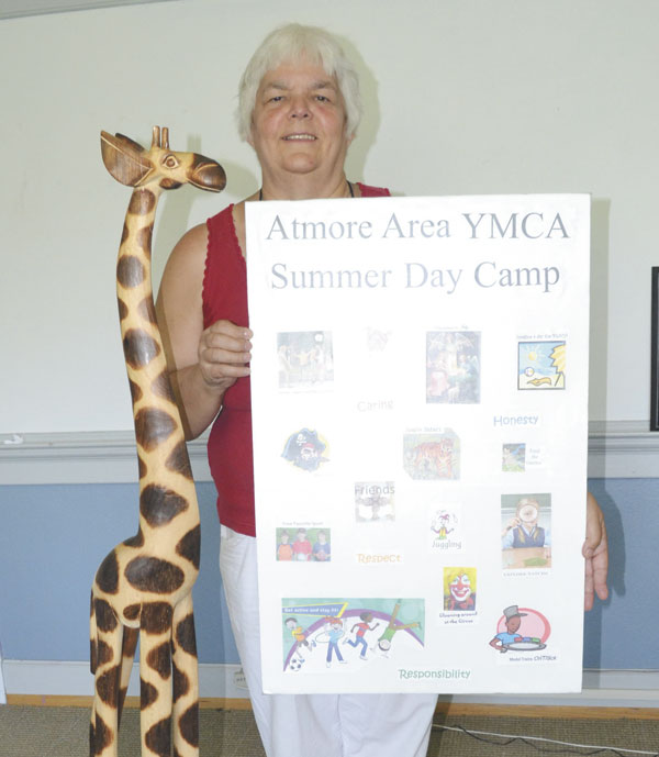 """New YMCA camp director Donna Vile shows off a poster of camp activities, and the camp's giraffe """"mascot."""""""