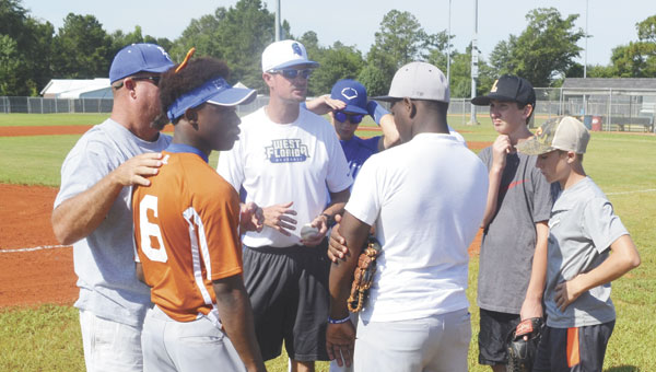 UWF head coach Mike Jeffcoat (in white shirt) talks to the campers and high-school coaches before Thursday's game.