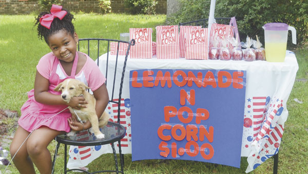 Lamaria Stallworth poses with her lemonade stand and her dog, Tip. She sold lemonade last week to buy supplies for her dog.|Photo by Allison Brown