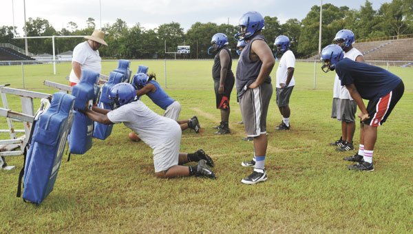 ECHS assistant coach B.J. Baker watches as several players practice their line technique with the blocking sled during Monday's practice. Monday was the first day that high-school teams are officially allowed to practice together in Alabama.
