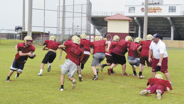 Northview High School football players execute a running play at practice Friday afternoon. Monday was the first day that teams can practice in full pads.