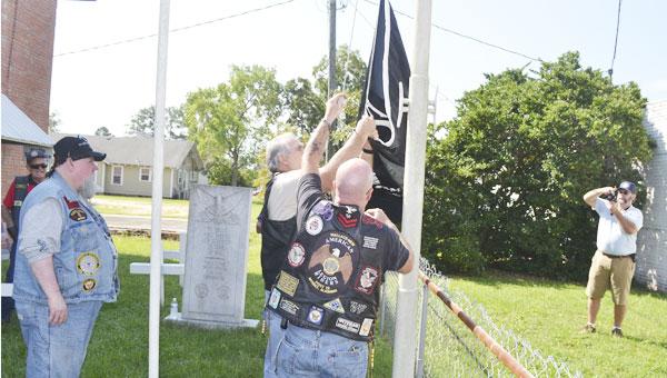 Atmore Post Commander Paul Chason takes photos while the American Legion Riders hoist the POW/MIA flag Tuesday.