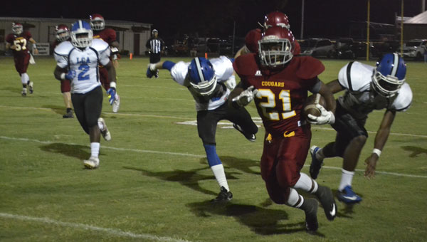 Escambia Academy's Gordon Brooks pulls away from Lancaster Christian Academy defenders to score a 64-yard touchdown reception early in the first quarter. The Cougars won 55-18, and Brooks scored two touchdowns.