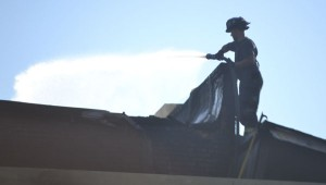 """At 8:30 a.m. Sunday, firefighters were still battling lingering """"hot spots"""" on the roof of the damaged building."""