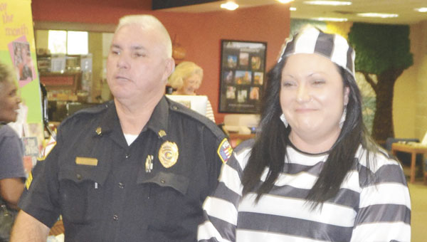 """Katie Harrison is """"arrested"""" by APD Sgt. Arthur Odom at the library Tuesday."""