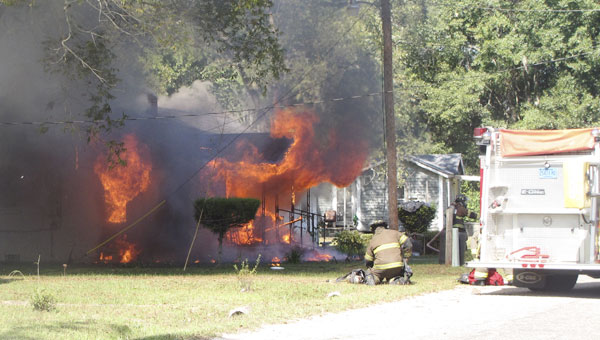 Firefighters battle a house fire on Mobile Street on Tuesday afternoon.|Photo by Allison Brown