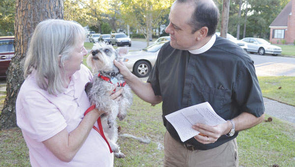 """The Rev. Mark McDonald gives a blessing to """"Annie,"""" held by Susan Tuthill."""