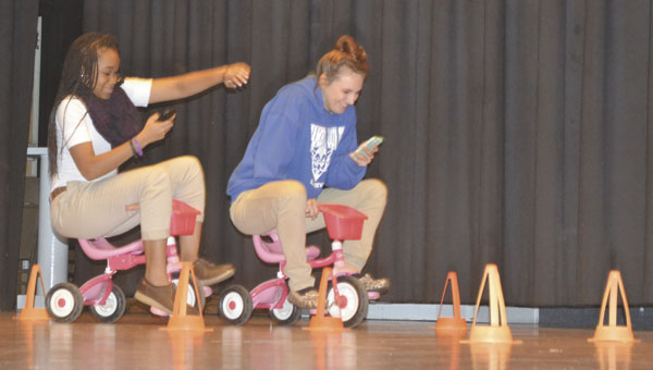 "ECHS students Kendal King and Cheyenne Chafin try to pedal a tricycle while sending a text message, during an activity at Thursday's ""It Can Wait"" program."