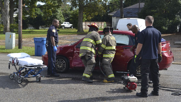 First responders work to remove the driver of a Ford Focus after a crash Thursday afternoon at the intersection of Main Street and Owens Street.