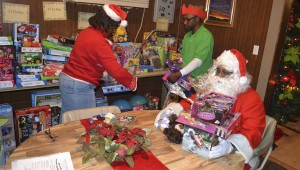 Volunteers Shelia Walker, Joseph Grimes and William Boggan help to organize the toys.