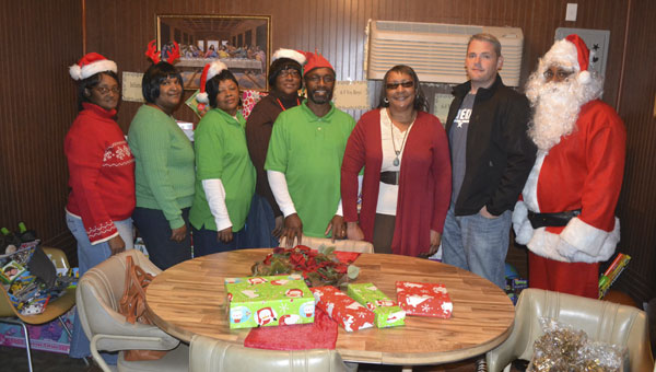 Some of the volunteers who helped with Saturday's toy give-away included, left to right, Shelia Walker, Sandra Boggan, Lucille Grimes, Debra Baldwin, Joseph Grimes, Betty Cox, Daniel White and Santa's helper, William Boggan.