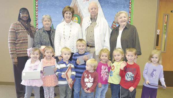 """Children in the """"Wee Kids"""" story time program show off the new iPads recently purchased through a grant. Also shown are Library Partners board members, left to right, Magaline Marshall, Sherry Digmon, Julie Johnson, Rex Rose and Myrna Monroe."""