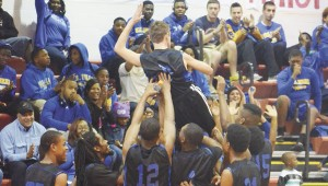 ECHS players lift Stephen Busby for a standing ovation after he hit a three-pointer against Flomaton earlier this month.|Photo by Adam Robinson, For The Advance
