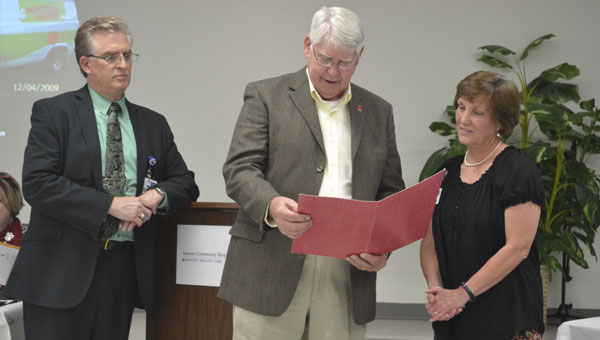 Atmore Mayor Jim Staff reads a city proclamation honoring Linda Lowrey's work career, as ACH administrator Bill Perkins listens.