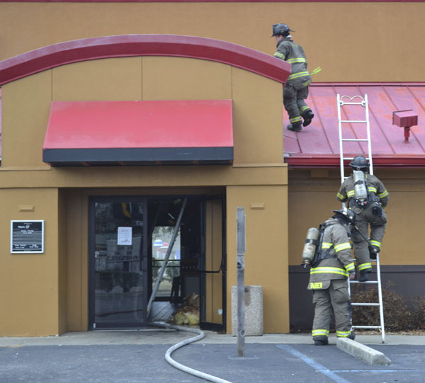 Firefighters climb onto the roof of the Atmore Pizza Hut to check on whether the fire was out.|Photo by Allison Brown