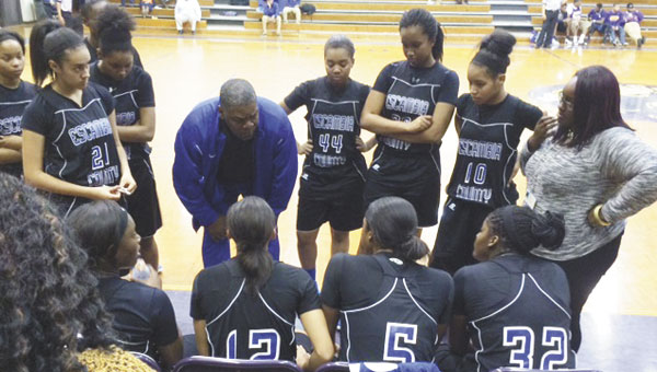 ECHS Lady Devils head basketball coach Jerome Webster goes over strategy with his players, during a timeout in last Tuesday's win at Jackson. It was the third area win of the season for the Lady Devils.