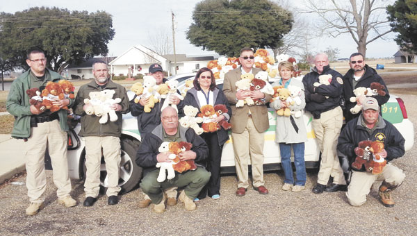 Shown with the bears are: standing, left to right, Officer Freddie Wells, Investigator Dale Lisenby, Lt. Jeffrey Weaver, Dispatcher Susan Rolin, Chief Larry Hammonds, Travel Plaza manager Tammy Smith, Officer Steve Griffis and Investigator Chris Rutherford; kneeling, left to right, Officer Alan Ward and Cpl. Roger Peebles.
