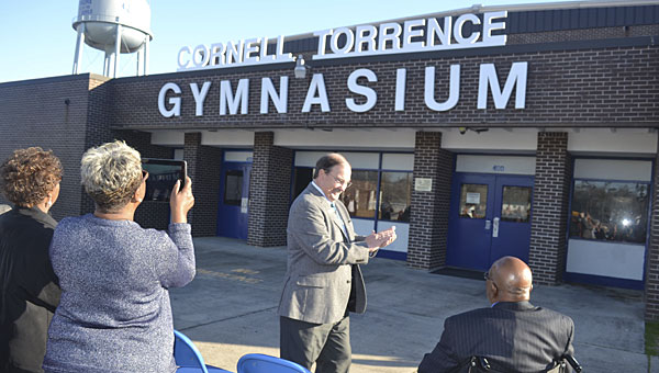 "County superintendent applauds Cornell ""Coach"" Torrence as the sign is unveiled renaming the Escambia County High School gymnasium in Torrence's honor Thursday afternoon."