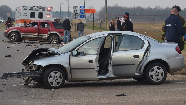 First responders work at the scene of a two-car accident that injured three people Monday afternoon at the intersection of Sunset Drive and State Highway 21 North.