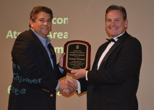 Muskogee Technology was named the 2014 Business of the Year. Tim Martin, president of Muskogee Technology, is shown accepting the award from chamber vice president Bub Gideons.