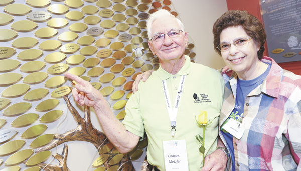 """Celebrate Life 2015 celebrant Charles Metzler of Atmore and his wife, Bertha, stand next to the """"Tree of Life"""" located in Cancer Treatment Centers of America at Southeastern's lobby. Celebrants' names are inscribed on the leaves of the tree, which serves as a lasting reminder of the courage and strength of cancer survivors."""