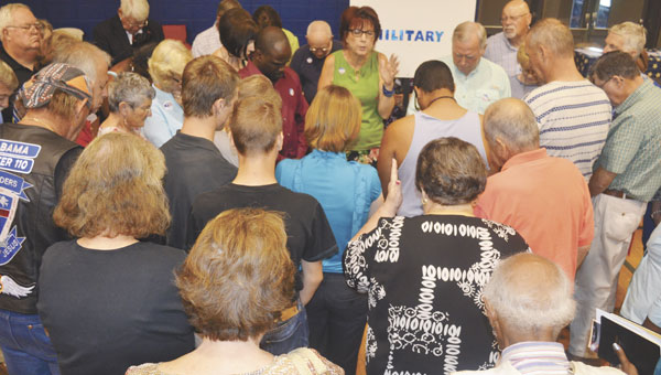 The Rev. Debora Bishop, pastor of First United Methodist Church, leads a prayer for the military at Thursday's National Day of Prayer celebration at Escambia County High School.