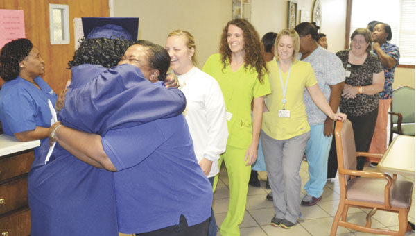 Atmore Nursing Center co-workers wait to give Dorothy McAroy a hug of goodbye and congratulations.