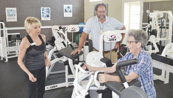 YMCA fitness director Maria Love-Davis and CEO Paul Chason look on as Carolyn Coleman tries out some of the new Cybex equipment at the YMCA.
