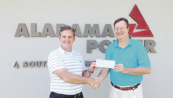 Bub Gideons, left, 2015 United Fund president, receives a $1,672 donation from Ricky Martin, branch manager for Alabama Power.