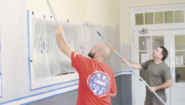 Ensley Lowe's employees Corey Wilborn and Rod Mette work to paint the hallway near the fitness center Thursday morning.