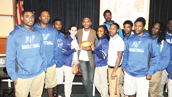 Former Escambia County Blue Devil, University of Alabama All-American and Miami Dolphin football player Don McNeal (center with football) poses for a picture with ECHS senior football players and cheerleaders. Below: McNeal signs the golden football. | Andrew Garner/Atmore Advance
