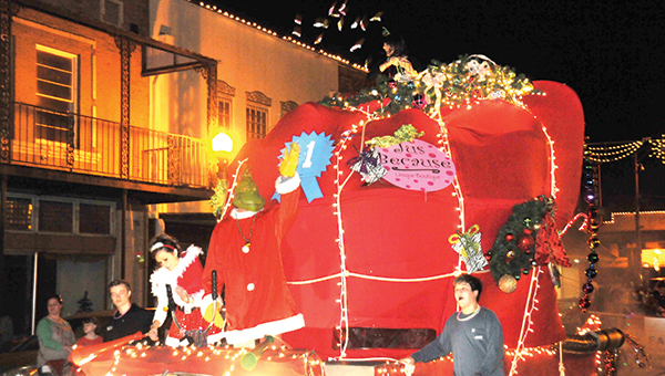 The Grinch on Jus Because's float throws candy out to the large crowd that attended the annual Twilight Christmas Parade Saturday night. | Andrew Garner/Atmore Advance