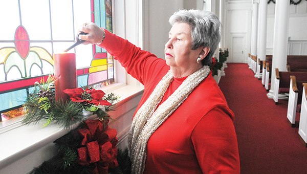 Katie Smith with First Baptist Church gets a candle wick ready for the Christmas Eve service. | Andrew Garner/Atmore Advance