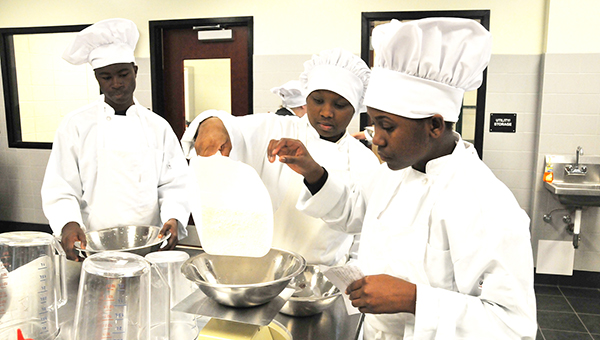 Marvin Lawson, Tyeisha Hall and Angel Judson measure flour for buttermilk pancakes. | Andrew Garner/Atmore Advance