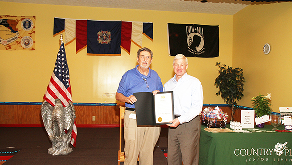 State Rep. Alan Baker hands a BBQ Competition proclamation to Walt Butler.   Submitted photo