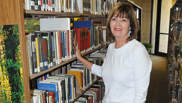 Cathy McKinley stands in the middle of a row of books at the library. | Andrew Garner/Atmore Advance