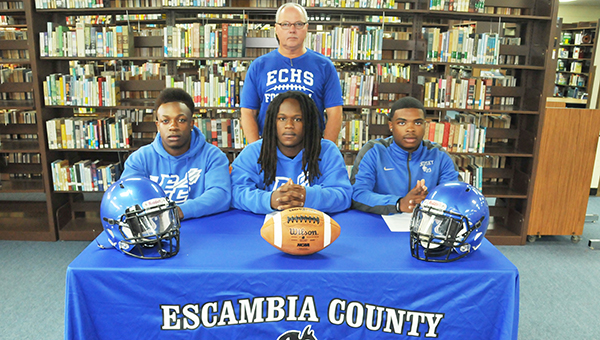 Escambia County's Devante Dailey, Gaetyn Thames and Rashaan Flavors signed to play football at the next level. All three are shown with ECHS football coach Royce Young. | Andrew garner/Atmore advance