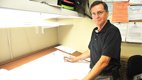 Richard Maxwell, owner of Maxwell Construction Co., stands next to his drawing station inside of his office. Maxwell Construction Co. has laid the foundation of many homes and businesses in Atmore. | Andrew Garner/Atmore Advance
