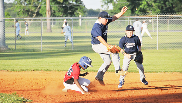All-Stars shortstop Josh Burkett (left) jumps over a Monroe County player during district action last week.   Andrew Garner/Atmore Advance