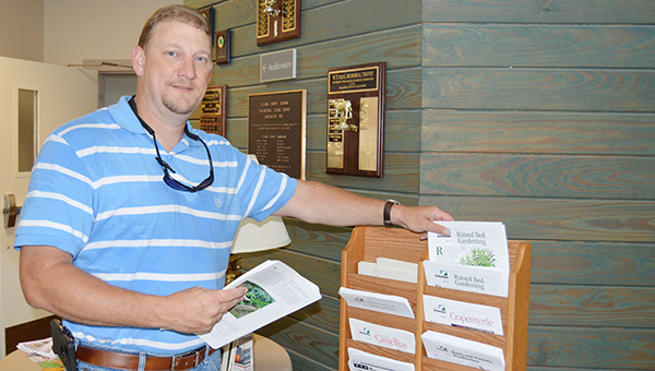 Anthony Wiggins, new Escambia County Extension agent, stocks the front lobby of the office on Ag Science Drive Tuesday. |                           Stephanie Nelson/The Brewton standard