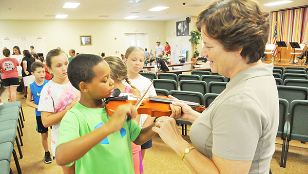 Pensacola Symphony Orchestra Violinist Allison Giltinan (right) helps Fred Barnhill play the violin during the camp at the Poarch Creek Indian Boys and Girls Club. Bottom: Students listen to a brass selection. | Andrew Garner/The Atmore Advance