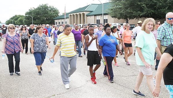 Above: Participants walk in front of Atmore City Hall Sunday at the start of the Love Walk. Below: Atmore Police Officers Jesse Traweek and Thaihee Staples give a thumbs up during the walk. | Photos by Walt Butler, Andrew Garner/Atmore Advance