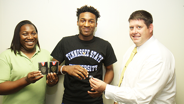 Former Escambia County track and field athlete Anthony Fountain picked up his Class 5A triple jump state championship ring last week at the high school. Fountain also finished second in the long jump during last year's state meet. Fountain, shown here with his mother, Brenda Andrews, and ECHS Principal Dennis Fuqua, is attending Tennessee State University in Nashville, Tenn. | Walt Butler/Atmore ADvance