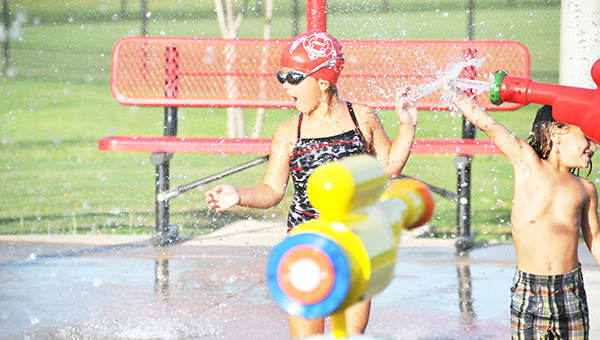 Kids utilized the Poarch Creek Indians' splash pad last Thursday during a swim meet at the recreation department. Top: Knox Wiggins guides the spray onto his sister, Aubree.   Andrew Garner/Atmore Advance